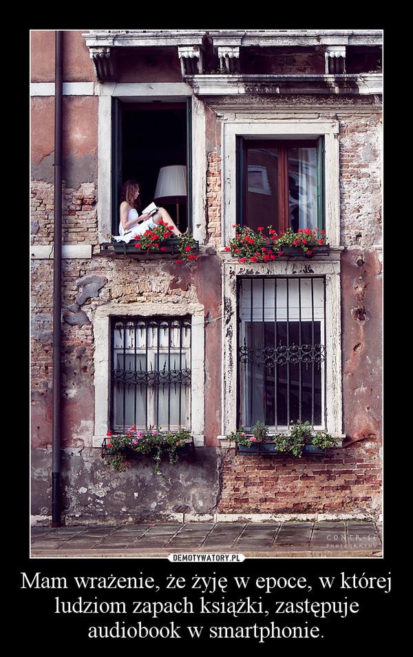 Фото девушка сидит в окне маленького дома и читает книгу.